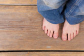 Barefoot girl standing on wooden floor — Stock Photo
