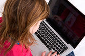 Young girl looking at laptop screen — Stock Photo