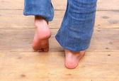Barefoot girl walking on wooden floor — Stock Photo
