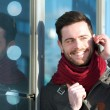Smiling man talking on phone outdoors — Stock Photo