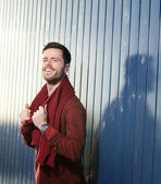 Man smiling outdoors with sweater and scarf — Stock Photo