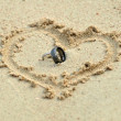 Wedding rings laying in sand in heart shape — Foto Stock