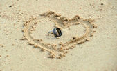 Wedding rings laying in sand in heart shape — Stock Photo