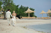 Bride and groom walking on caribbean beach — Stock Photo