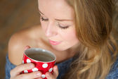Beautiful young woman enjoying cup of tea at home — Stock Photo