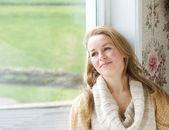 Woman sitting by window looking outside — Stok fotoğraf