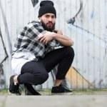 Urban man sitting by graffiti — Stock Photo