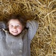 Girl smiling and lying down on hay — Stock Photo