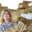 Cute young girl playing in the hay — Stock Photo