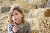 Cute girl sitting alone on haystacks  — Stock Photo