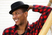 Smiling young black man with hat — Stock Photo