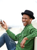 Man smiling outdoors with mobile phone  — Stock Photo