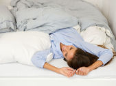 Young woman awake in bed smiling — Stock Photo