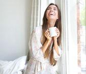 コーヒーを飲む窓笑顔の女性 — ストック写真