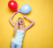 Young woman celebrating with balloons — Stock Photo
