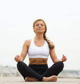 Young woman sitting in yoga pose outside — Stock Photo