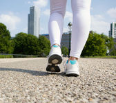 Young woman feet walking in city park — Stock Photo