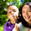 Smiling mother with son blowing dandelion — Stock Photo