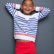 Little black boy smiling with hands behind head — Stock Photo