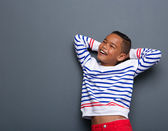 Young boy smiling with arms behind head — Stock Photo