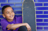 Cute kid smiling outdoors with skateboard — Stock Photo