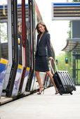 Young business woman embarking on train — Stock Photo