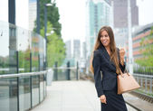 Business woman smiling at outdoor train station — Stock Photo