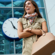 Young woman smiling outside building with clock — Stock Photo #47363719