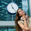 Young woman thinking with clock in background — Stock Photo #47363733