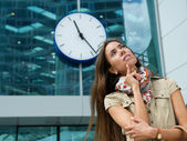 Young woman thinking with clock in background — Stock Photo