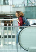 Woman smiling with bag on escalator — Stock Photo