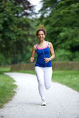 Woman running on footpath in the park  — Stock Photo