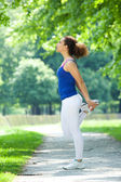 Young woman stretching on footpath  — Stock Photo