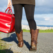 Woman holding bag and walking on road — Stock Photo #47826529