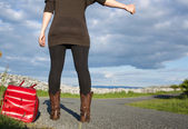 Woman with bag hitchhiking — Stock Photo