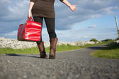 Woman hitchhiking with bag  — Stock Photo