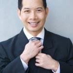 Smiling businessman holding necktie — Stock Photo #48140321