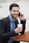 Young man smiling with phone and coffee — Stock Photo