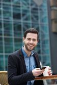 Cute guy smiling with mobile phone — Stockfoto