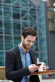 Man smiling with phone at outdoors cafe — Foto de Stock
