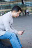 Asian man sitting with cellphone  — Stock Photo