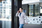 Man exiting building with mobile phone — Stock Photo