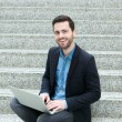 Young man sitting on steps and smiling with laptop — Stock Photo #49733141