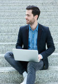 Young man sitting on steps with laptop — Stock Photo