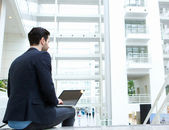Businessman sitting indoors with laptop — Stockfoto