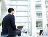 Empresário sentado dentro de casa com laptop — Foto Stock