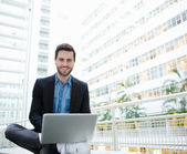 Friendly young man using laptop — Stock Photo