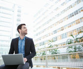 Businessman sitting with laptop inside building — Zdjęcie stockowe