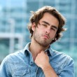 Attractive young man posing outdoors — Stock Photo #50081135
