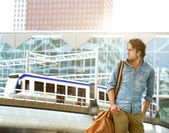 Fashionable young man traveling with bag — Stock Photo